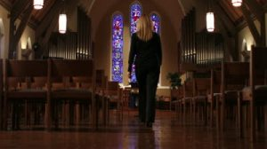 stock-footage-wman-entering-church-and-sitting-in-pew